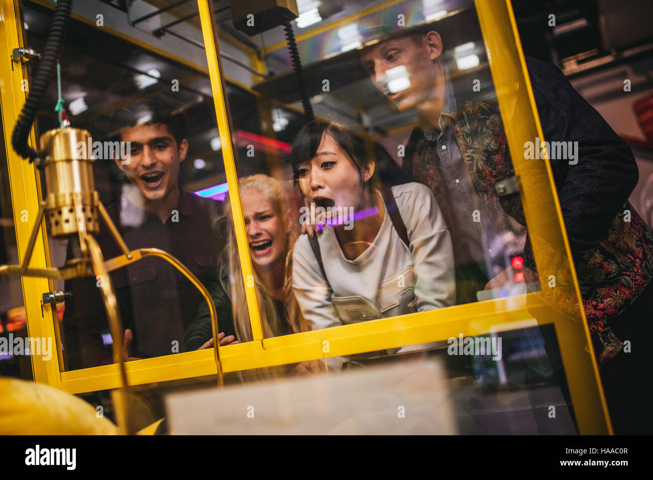 Excited young friends playing toy grabbing game at amusement park. Happy woman selecting a random soft toy in a - Stock Image