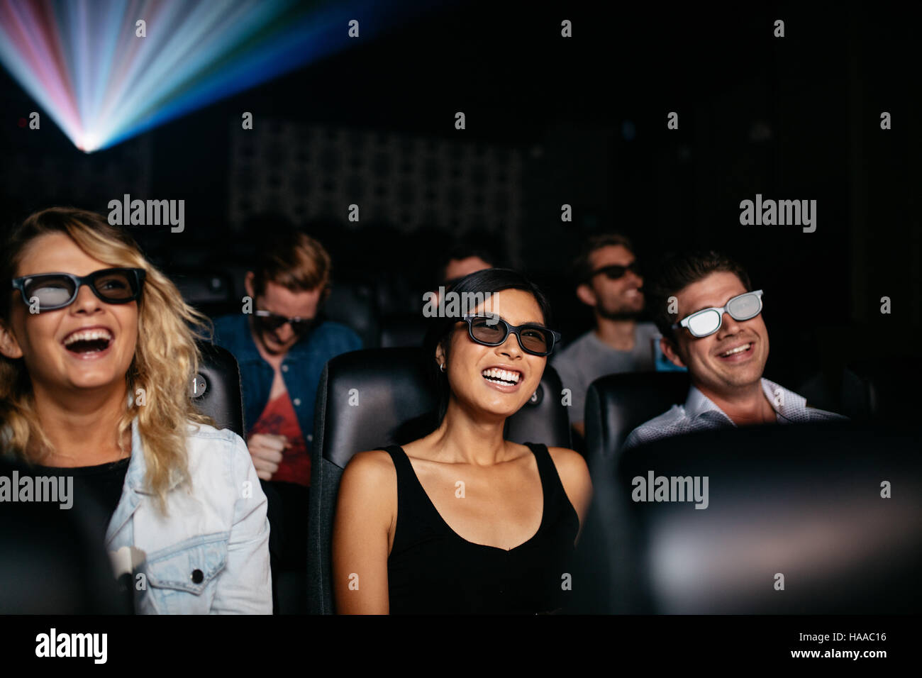 Group of young friends watching 3d movie in theater and laughing. Young men and women wearing 3d glasses in cinema - Stock Image