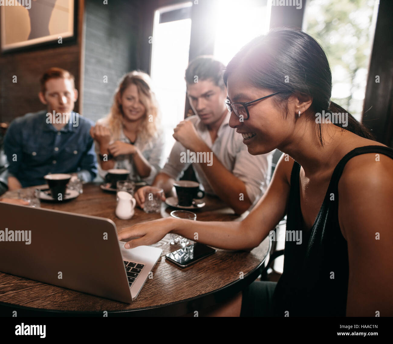 Group of friends in cafe watching something online on laptop. Young men and women at restaurant looking at laptop. - Stock Image