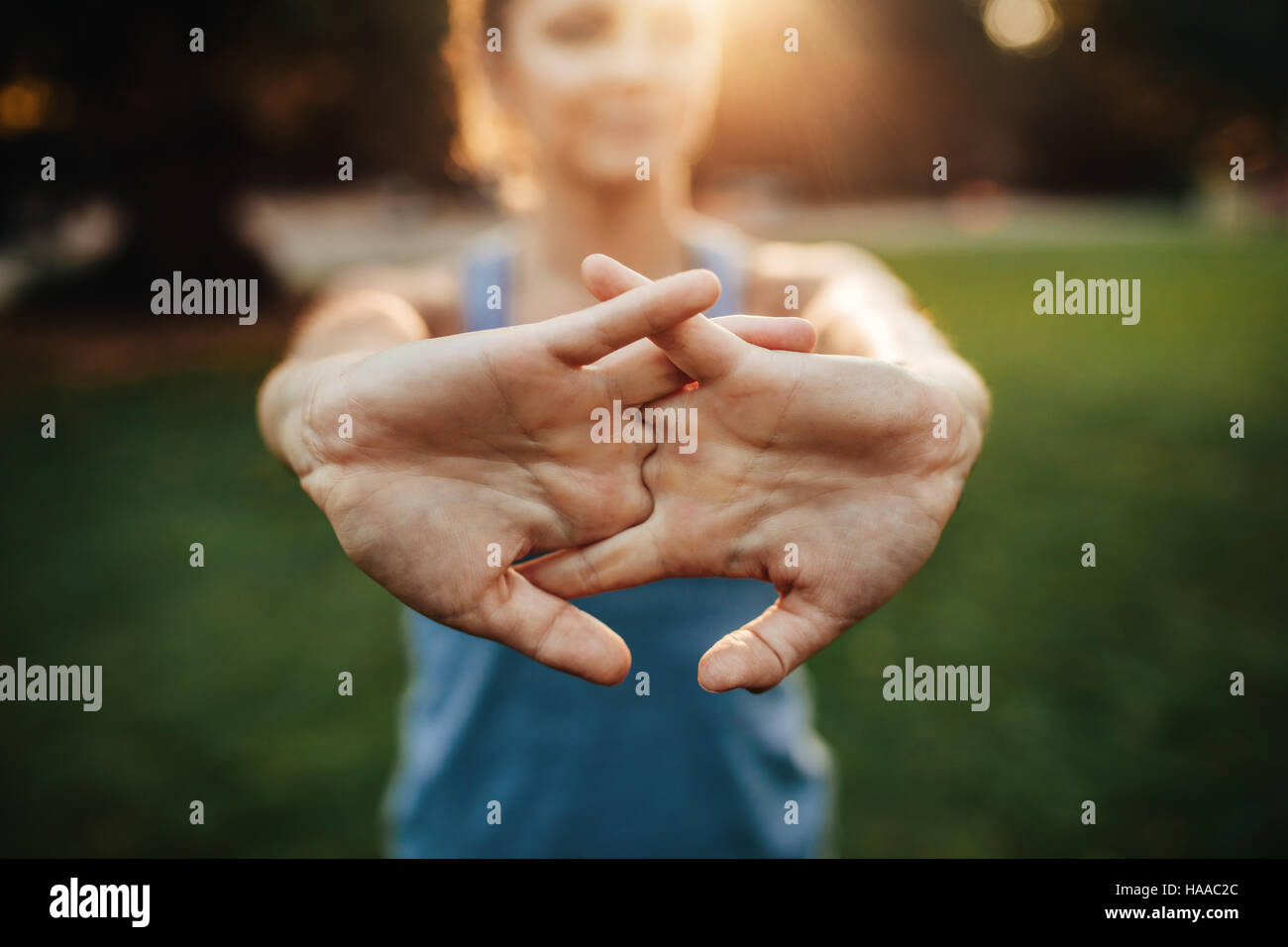 Young woman stretching arms outdoors. Fitness female doing warmup exercise at the park, focus on hands. - Stock Image