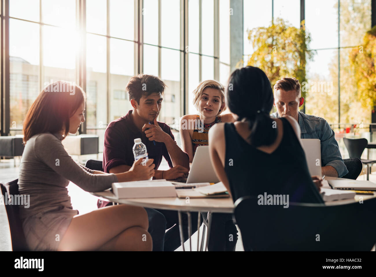 Young students sitting around a table in library with books and laptop. University students doing group study in - Stock Image