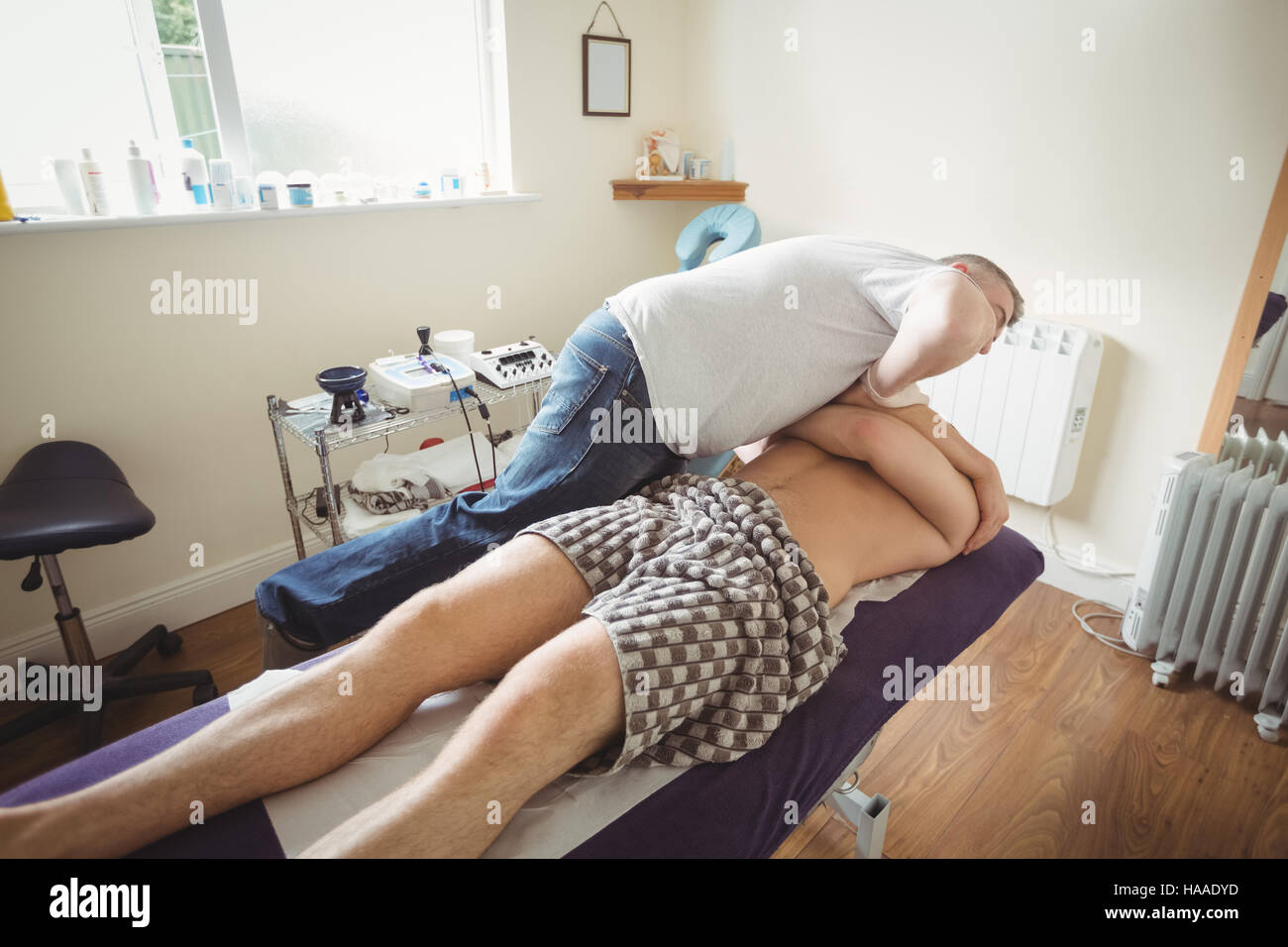 Physiotherapist examining shoulder of a patient - Stock Image