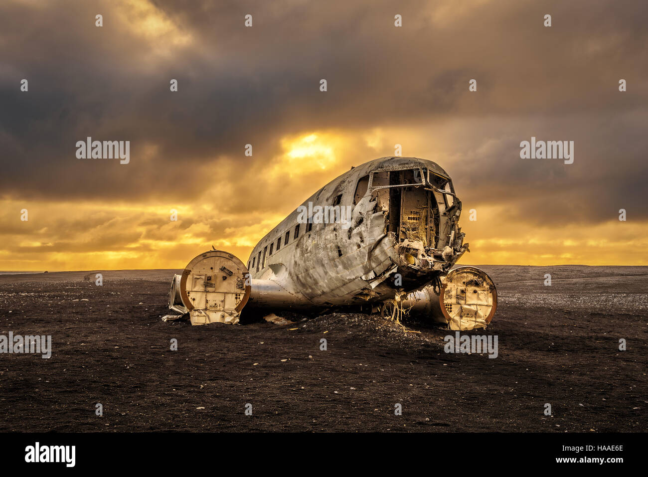 Old crashed plane abandoned on Solheimasandur beach near Vik in Iceland with heavy storm clouds in the sky. Hdr - Stock Image