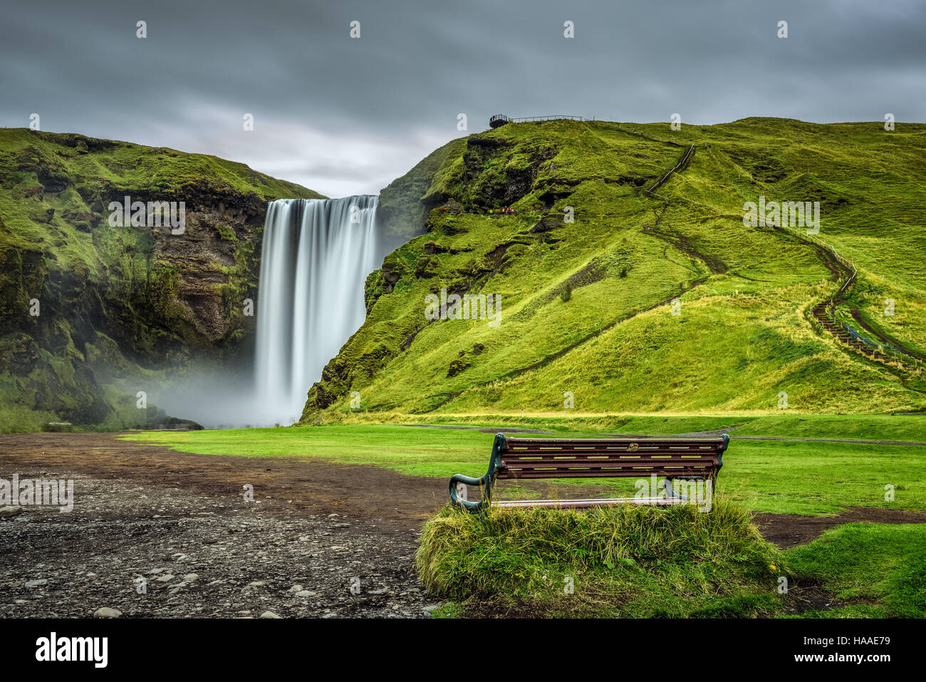 Bench at the famous Skogafoss waterfall in southern Iceland. Long exposure. - Stock Image