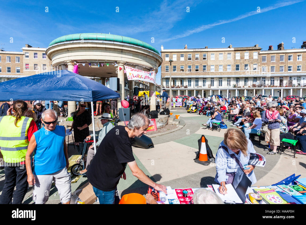 Jeremy Corbyn Momentum rally. Woman signing petition document at table. Background crowds and bandstand on the seafront - Stock Image