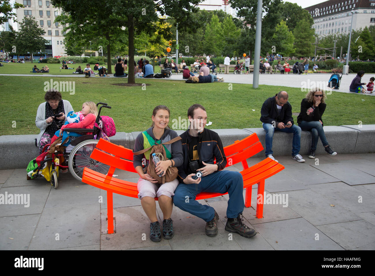 Couple sitting on one of the flourescent benches on the Southbank, London, United Kingdom. The South Bank is a significant - Stock Image