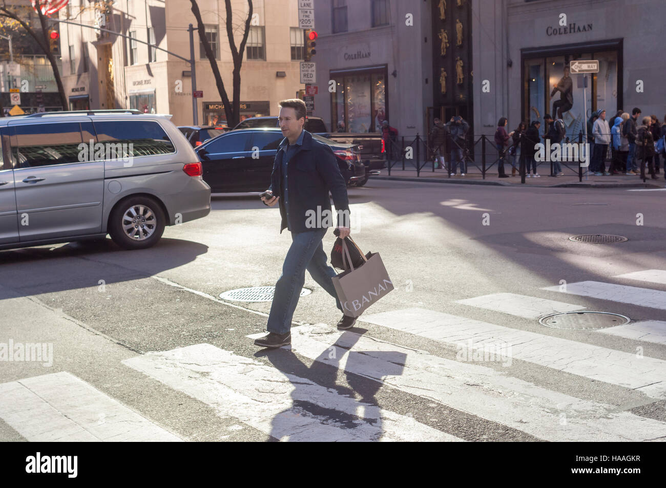Shopper crosses Fifth Avenue in Midtown Manhattan in New York on Sunday, November 27, 2016. The National Retail - Stock Image