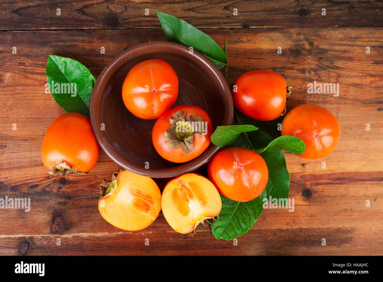 Persimmons kaki fruits on rustic table. Top view. - Stock Image