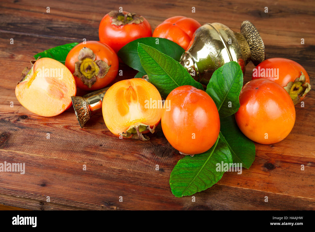 Persimmons kaki fruits with vintage brass vase. Oriental East Persian still life. - Stock Image