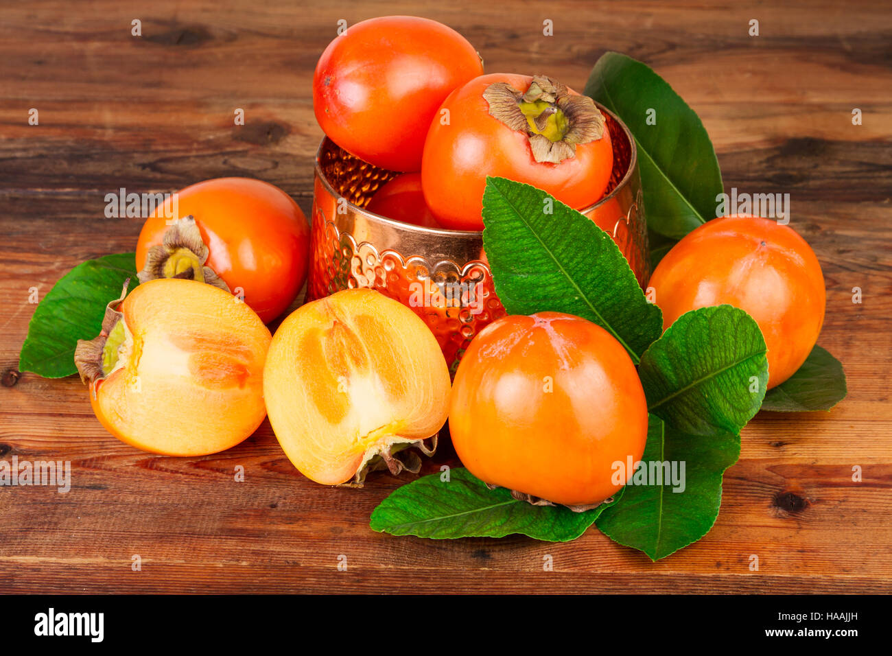 Persimmons with vintage copper vase on old wood. Oriental still life. - Stock Image