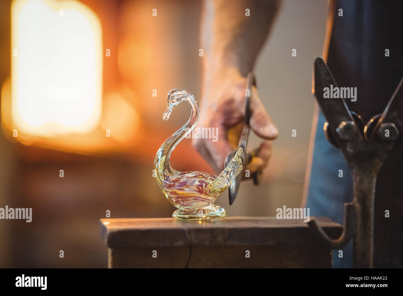 Glassblower shaping a molten glass - Stock Image