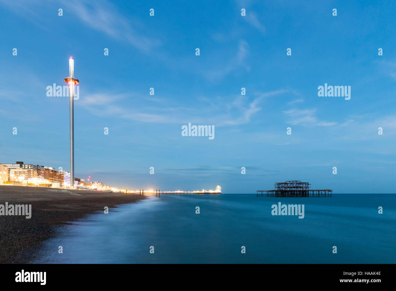 Night Photo of Brighton Skyline with old West Pier, Central Pier with fun fair lights and the new i360 attraction - Stock Image