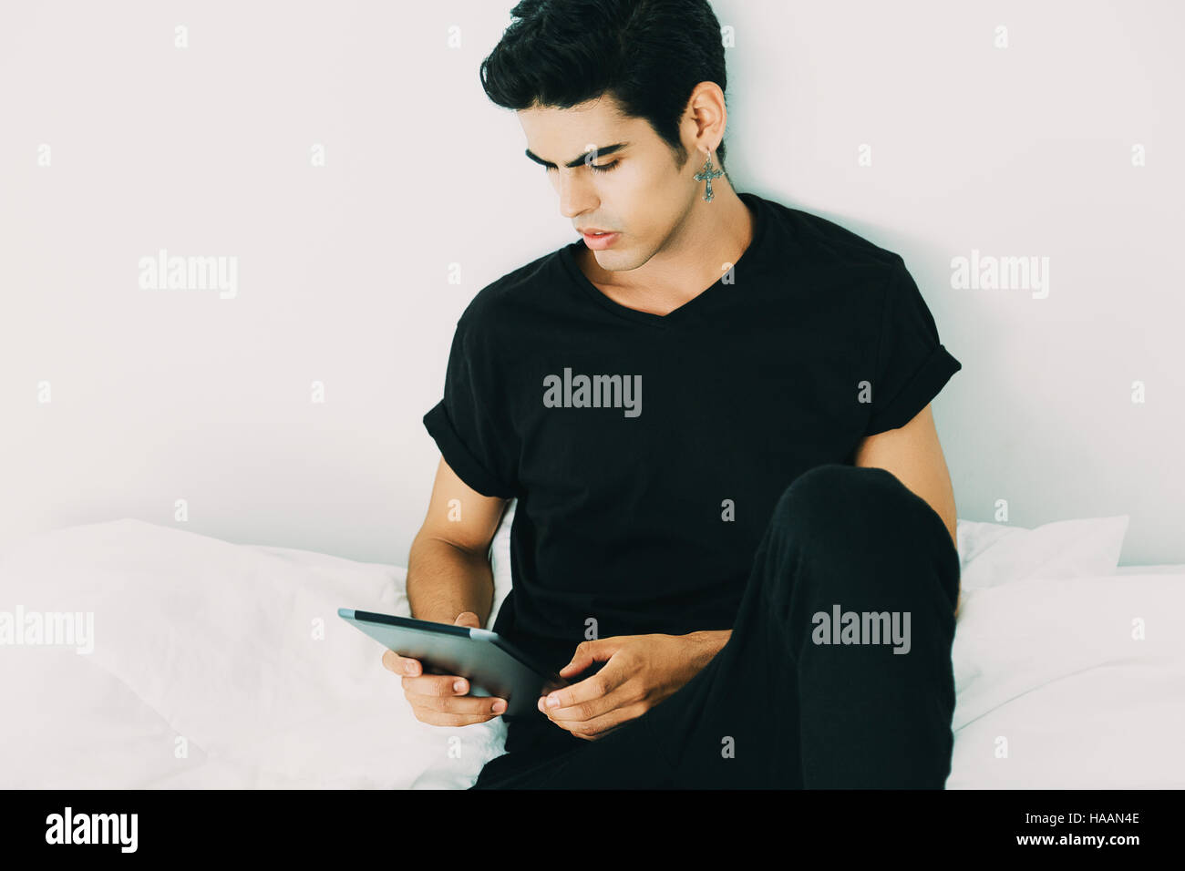 Handsome attractive brazilian guy with cross-earring in black t-shirt and tights is sitting on bed and using digital - Stock Image