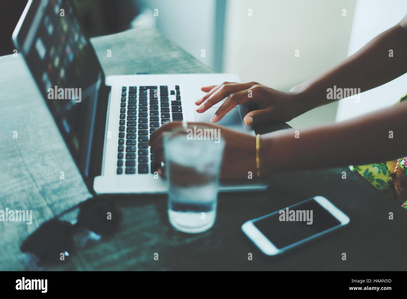 Side view of woman hands using laptop on a stone table with glass of water, smartphone and sunglasses on it, dark - Stock Image