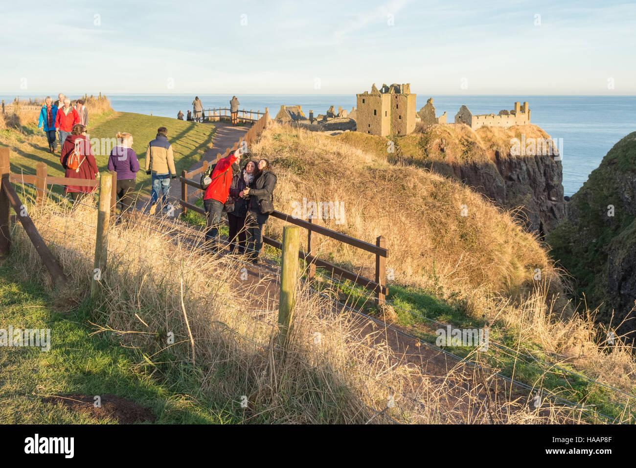 Dunnottar Castle, Stonehaven, Scotland - visitors enjoying the winter sunset - Stock Image