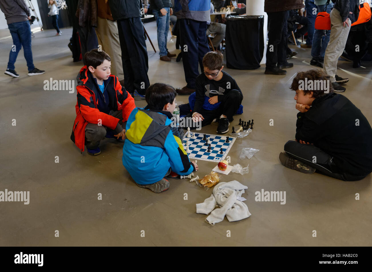 At the World Chess Championship, held in the South Street Seaport, some boys sat on the floor playing chess. Nov. - Stock Image