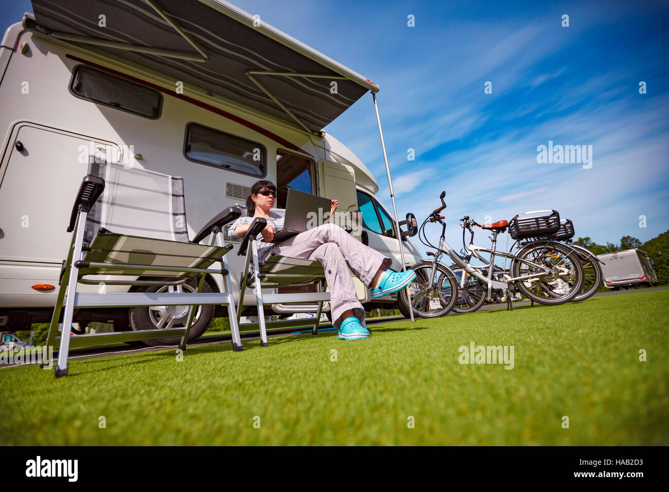 Woman sitting on a chair near the camper and looking at a laptop. Caravan car Vacation. Family vacation travel, - Stock Image