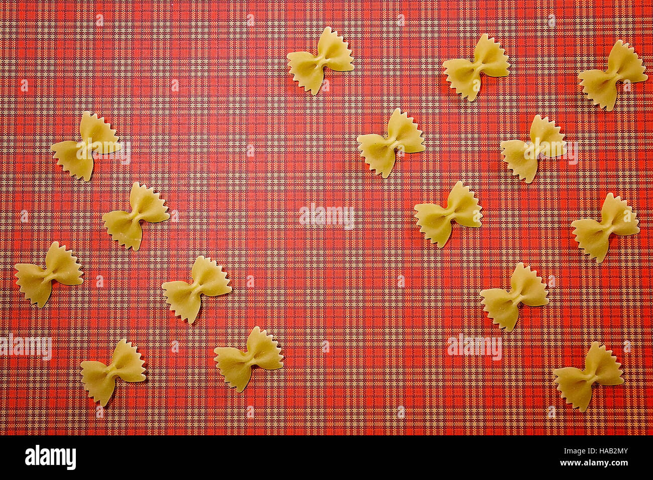 Pasta pattern background. Wholemeal bow tie farfalle on red squared tablecloth. Flat lay. Top view. - Stock Image