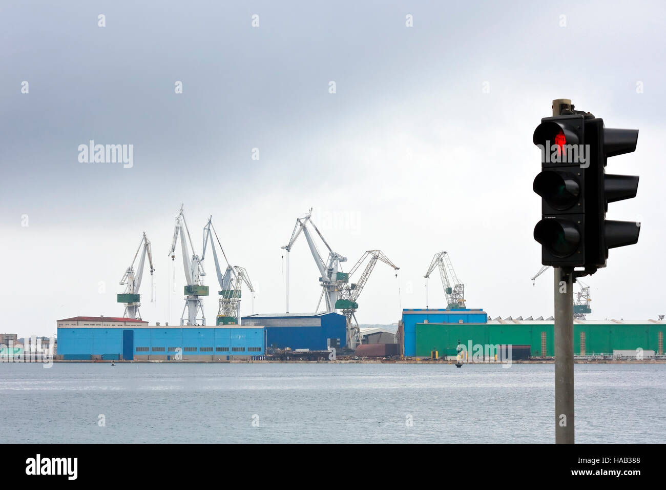 Still stand in ship industry with stoplight as symbol and dark clouds - Stock Image