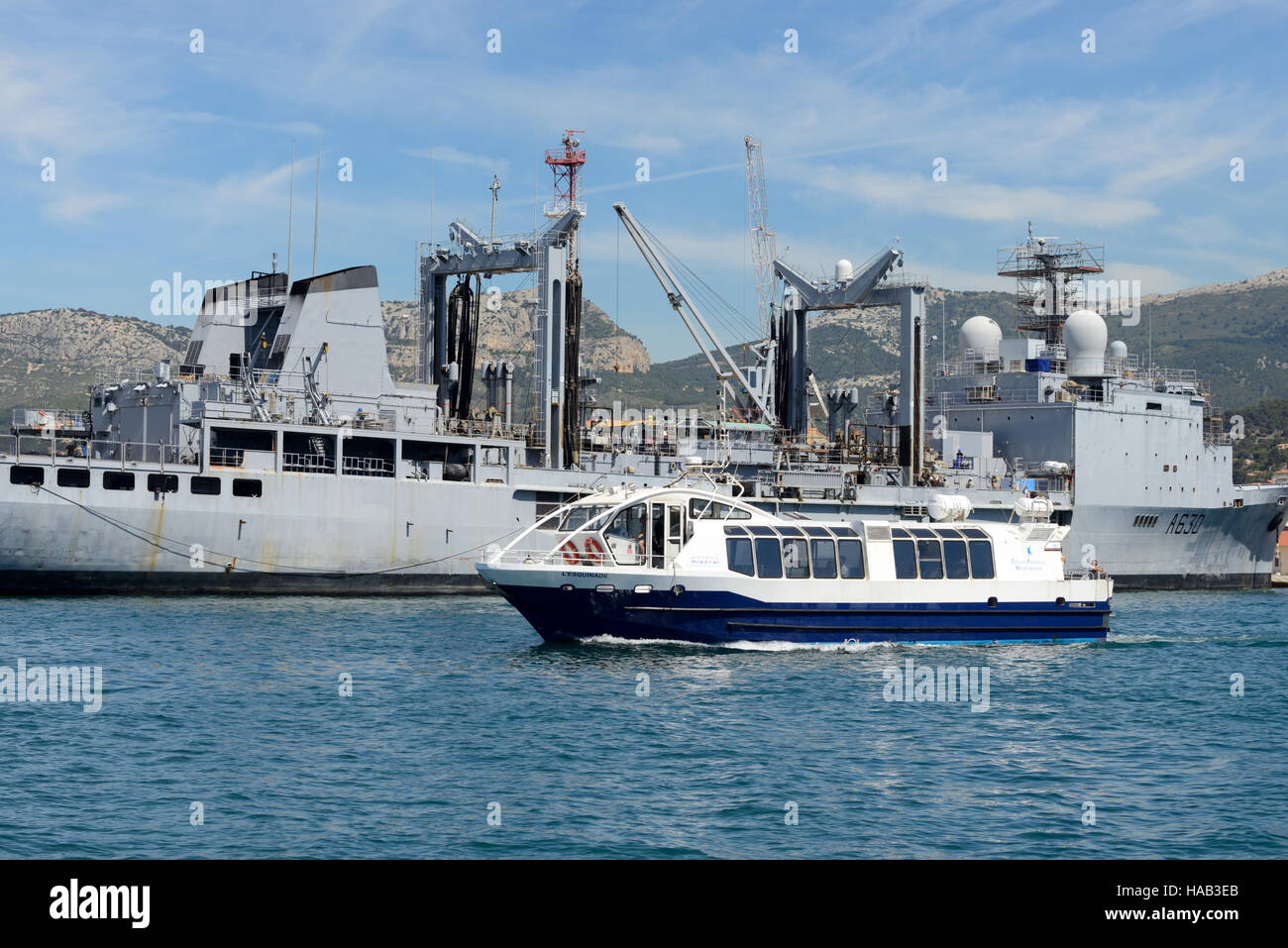 Ferry Boat Cruises Past the Marne Frigate or Warship of the French Navy in the Port of Toulon Provence France - Stock Image