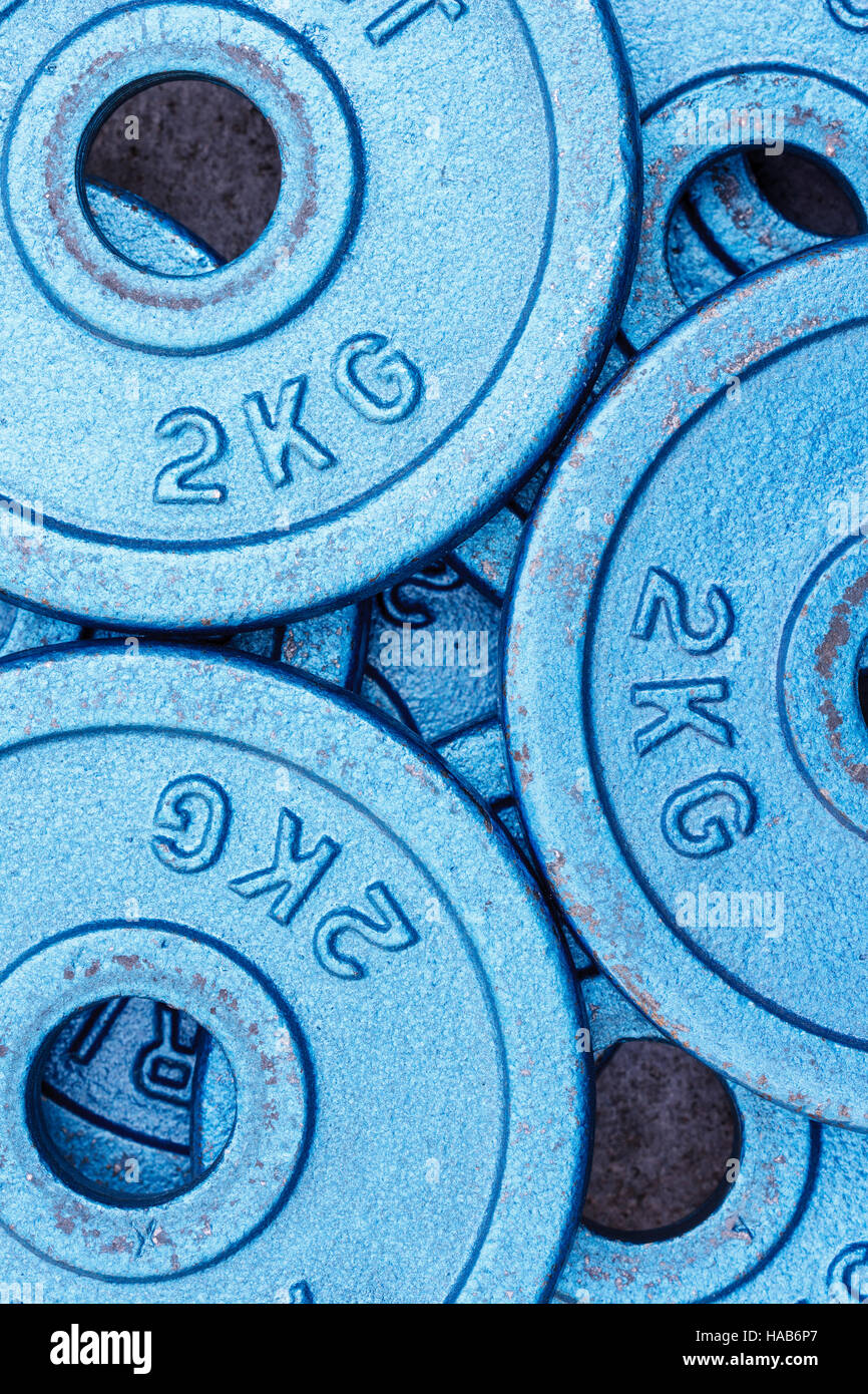 Blue weight plates of 2 kilograms stacked in an alternating pattern. - Stock Image