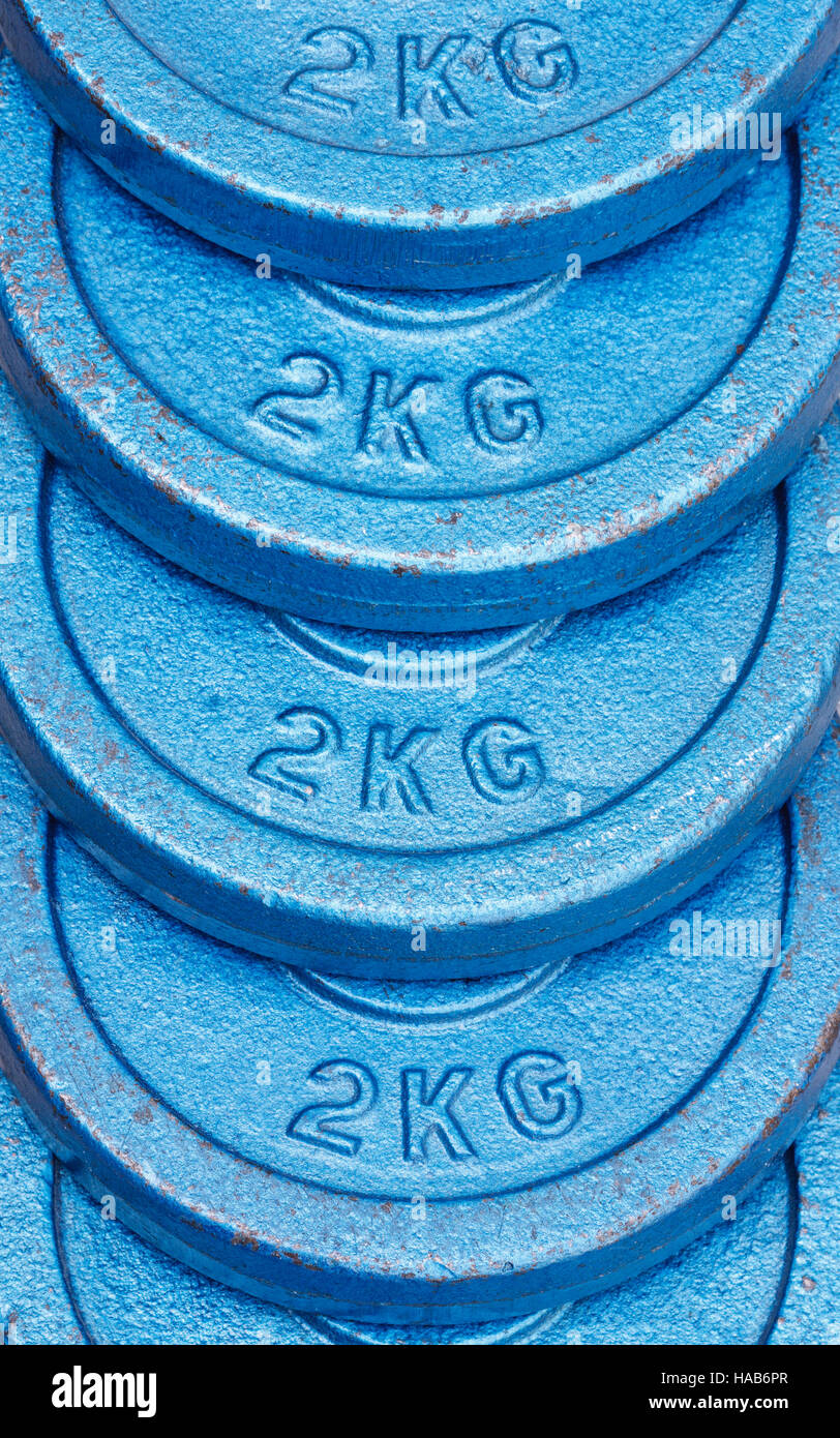 Stacked blue 2 kilogram weight plates - Stock Image