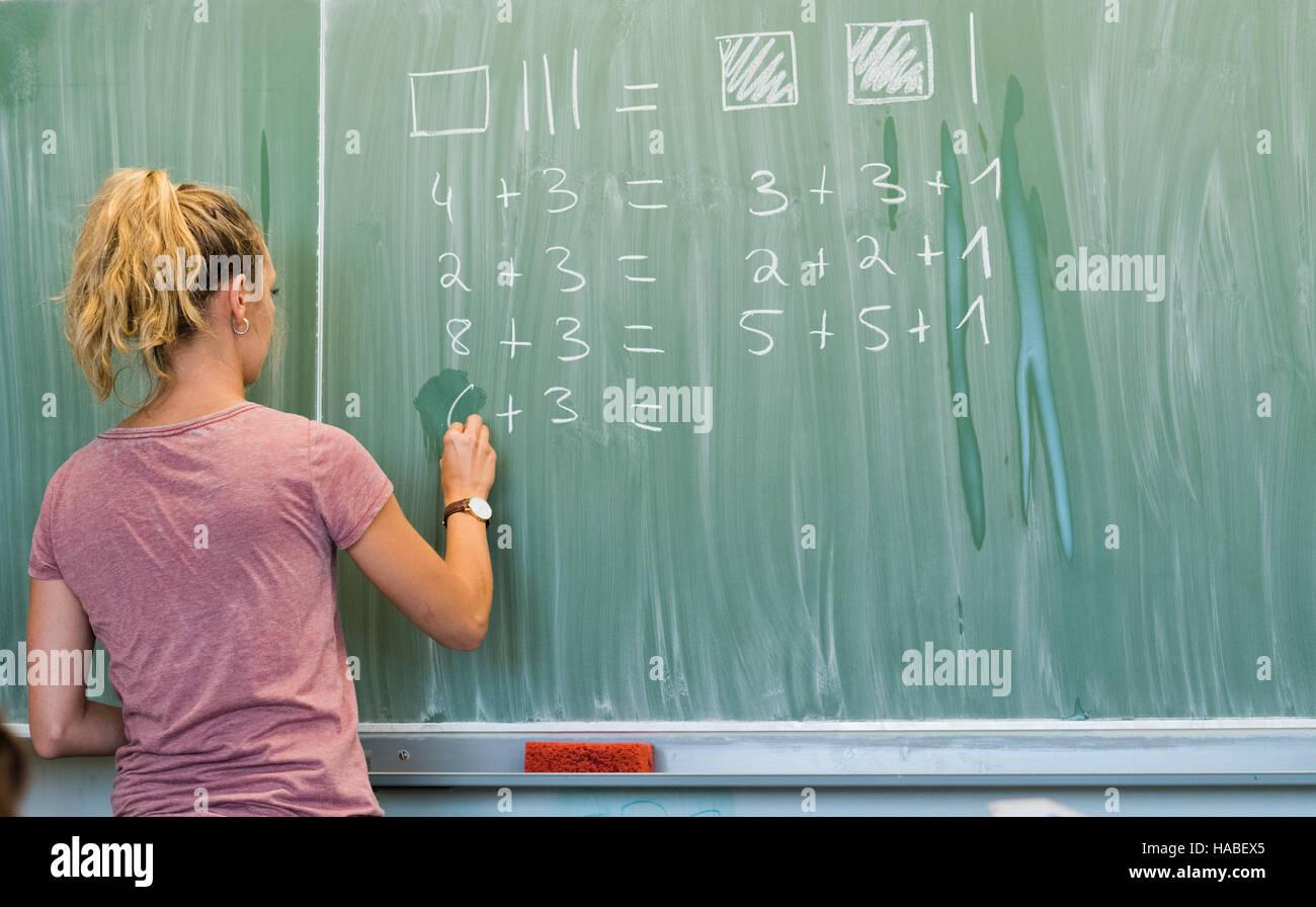 Hannover, Deutschland. 17th Aug, 2016. Eine junge Lehrerin schreibt am 17.08.2016 an eine Schultafel im Mathematikunterricht Stock Photo