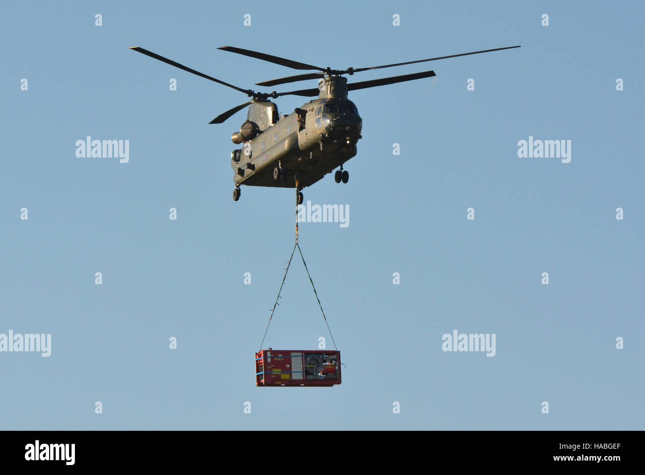 RAF Chinook carrying a High Volume Pump from Sandown Airport on the Isle of Wight during a multi-agency training - Stock Image