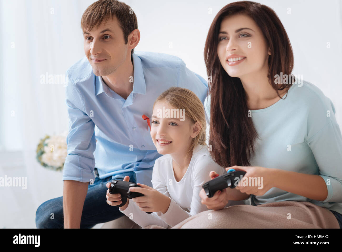 Nice close knit family playing video games - Stock Image