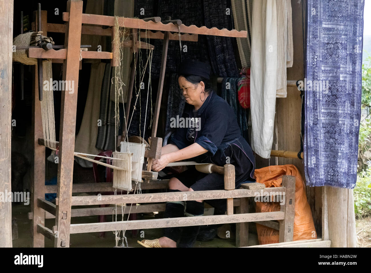 Black Hmong woman weaving on a loom in Cat Cat village, Sapa, Vietnam, Asia - Stock Image