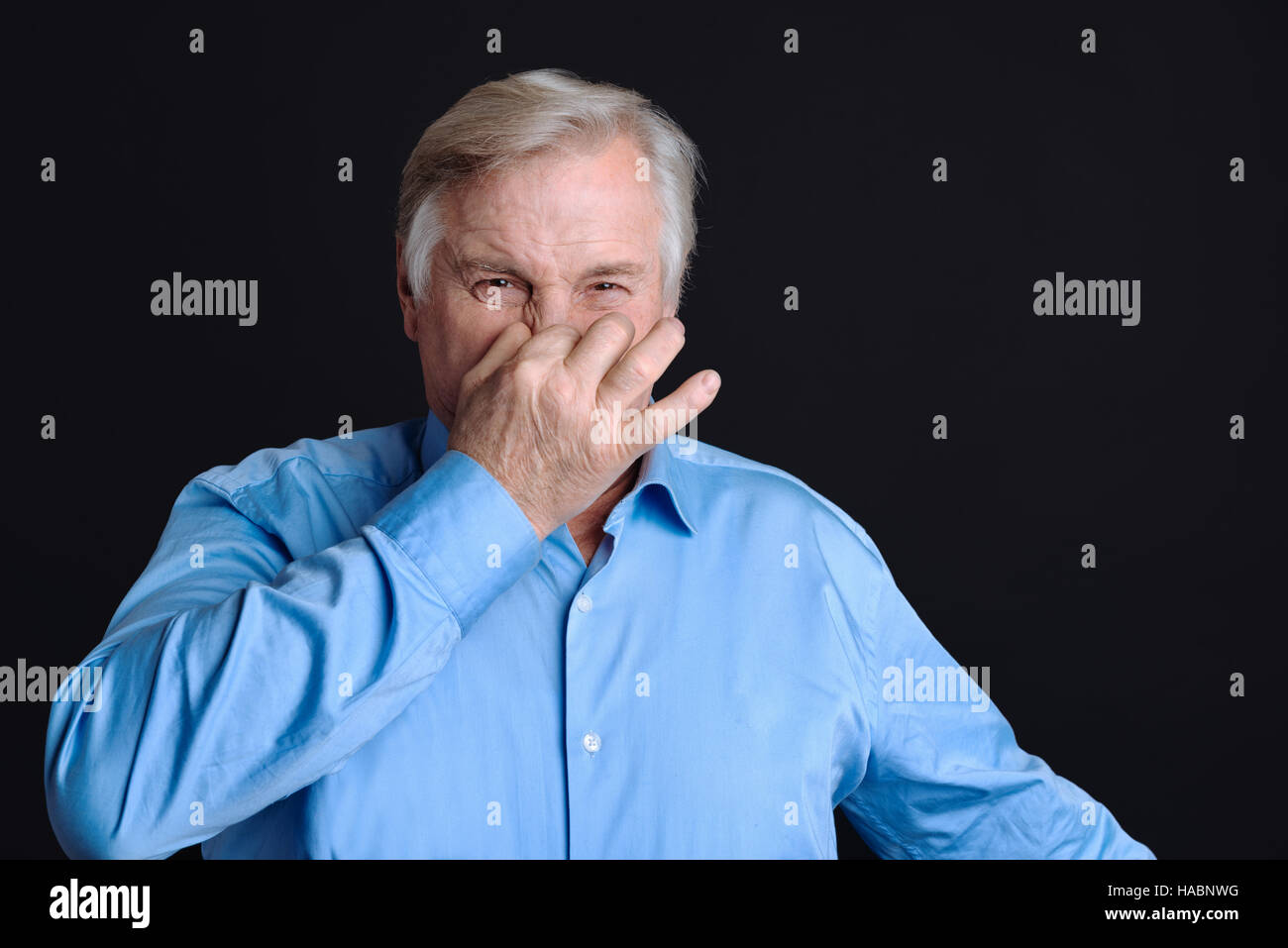 Old man pinches his nose with the disgust on face - Stock Image