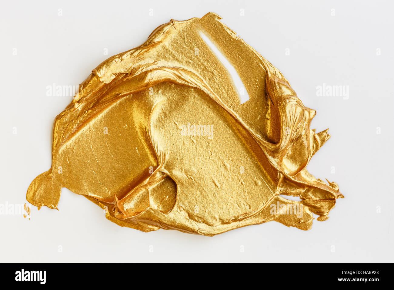 Gold acrylic paint on white background - Stock Image