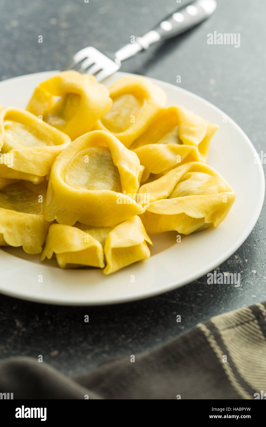 Italian traditional tortellini pasta on plate with fork. - Stock Image