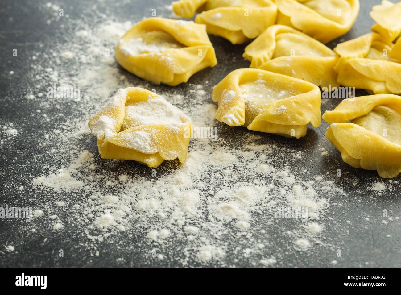 Italian traditional tortellini pasta and white flour. - Stock Image