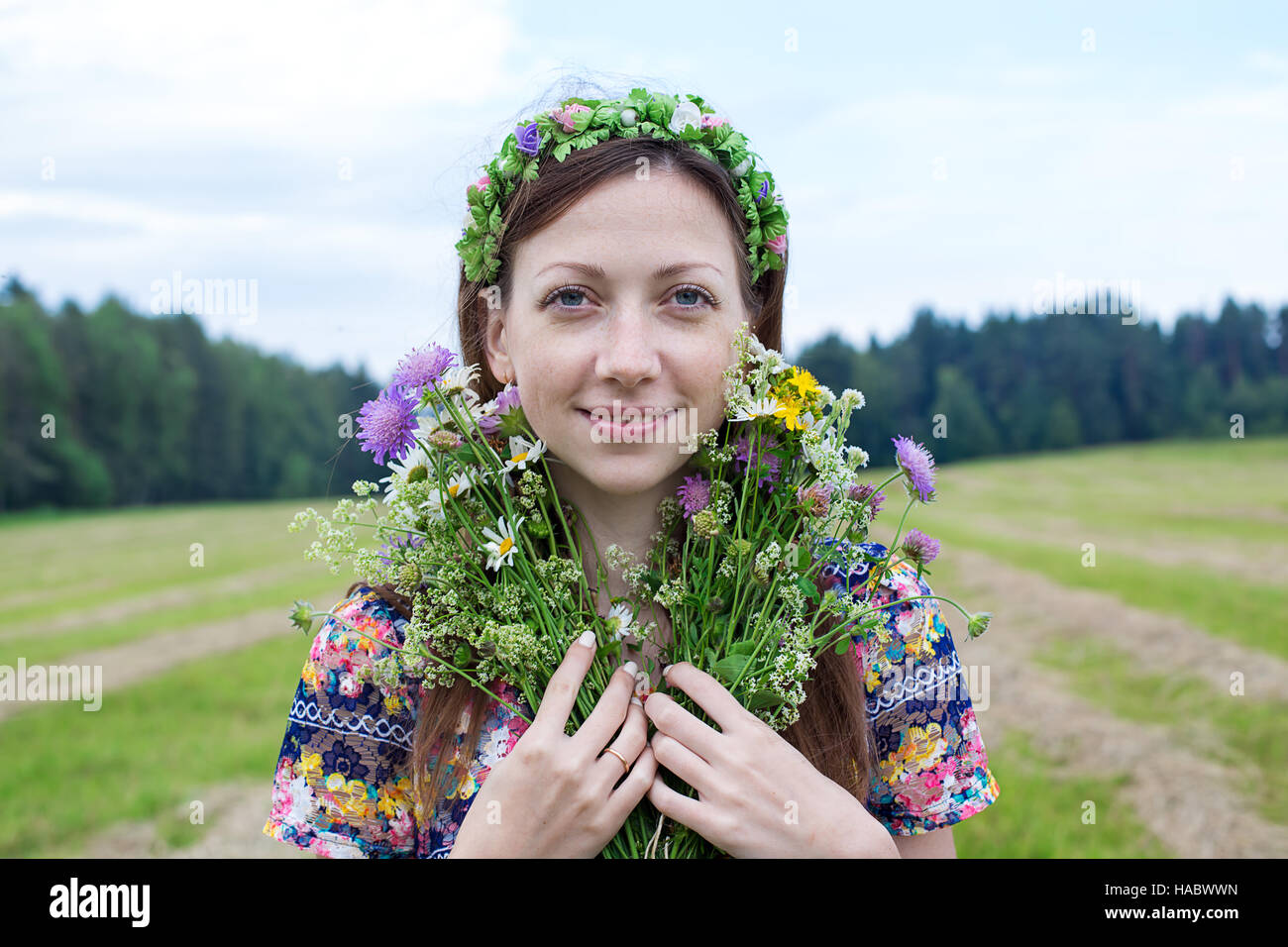 Freckled girl standing with splitting flower bouquet - Stock Image