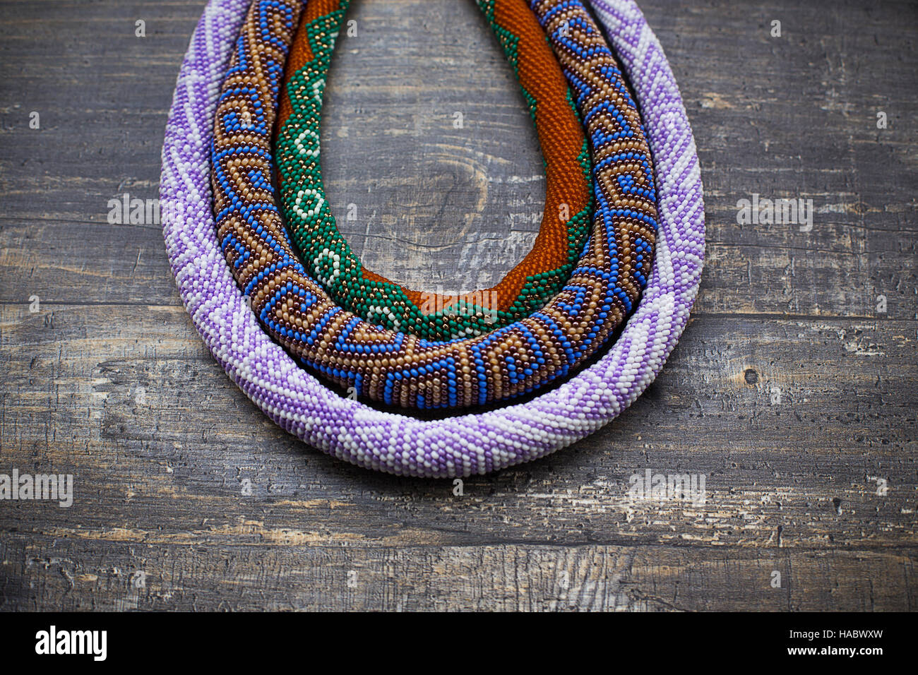 Three knitted beaded plaits on wooden background - Stock Image