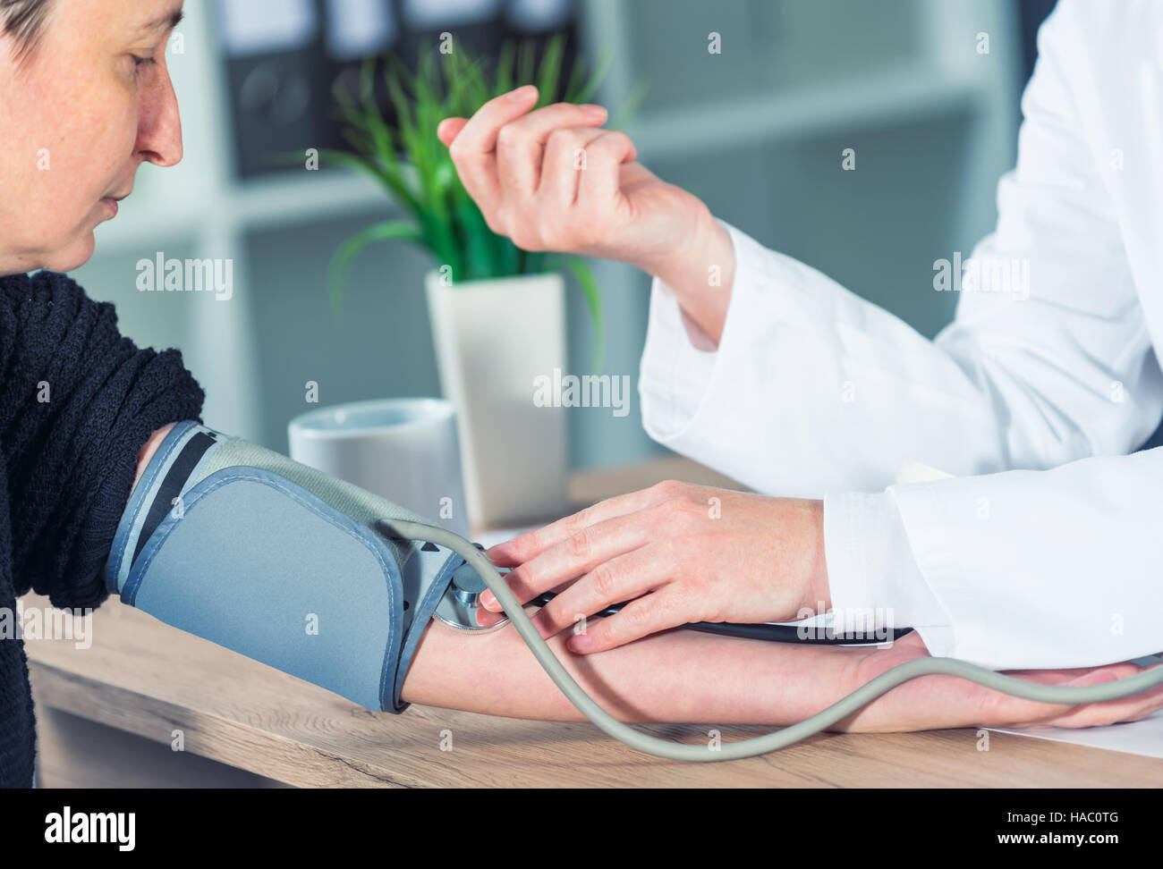 Doctor cardiologist measuring blood pressure of female patient in hospital office, health care control and monitoring - Stock Image