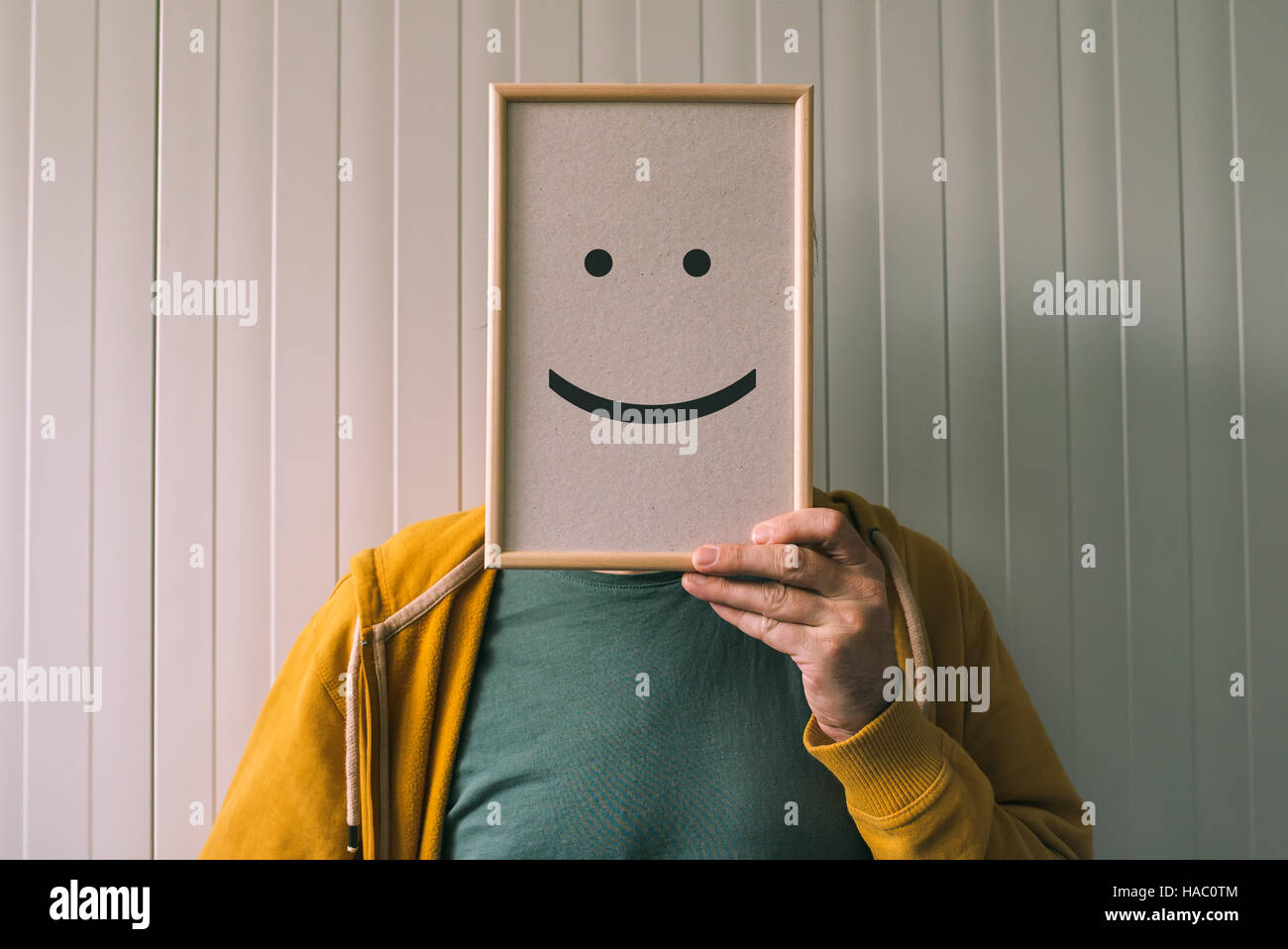 Put a happy face on, happiness and cheerful emotions concept, man holding picture frame with smiley emoticon printed - Stock Image