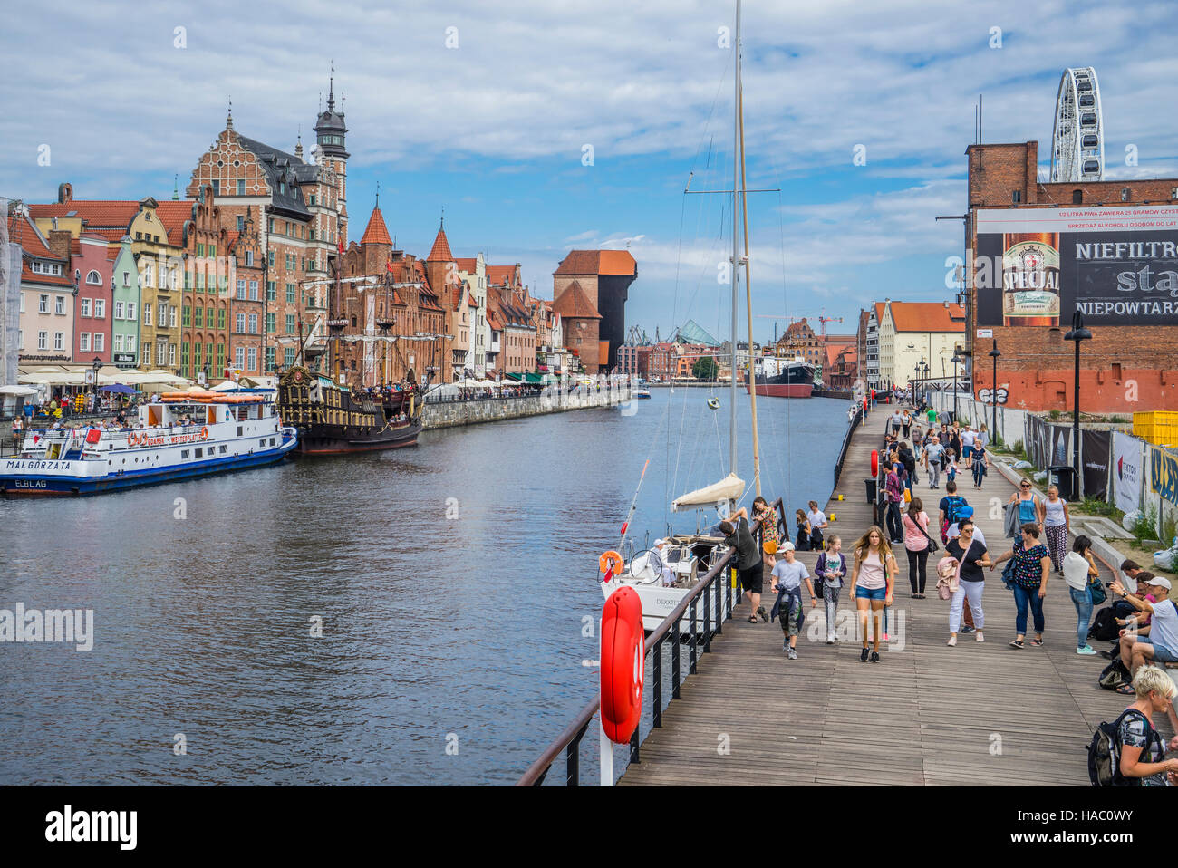 Poland, Pomerania, Gdansk, boardwalk on Granary Island with view of Mottlau River and the Long Bridge quayside promenade - Stock Image