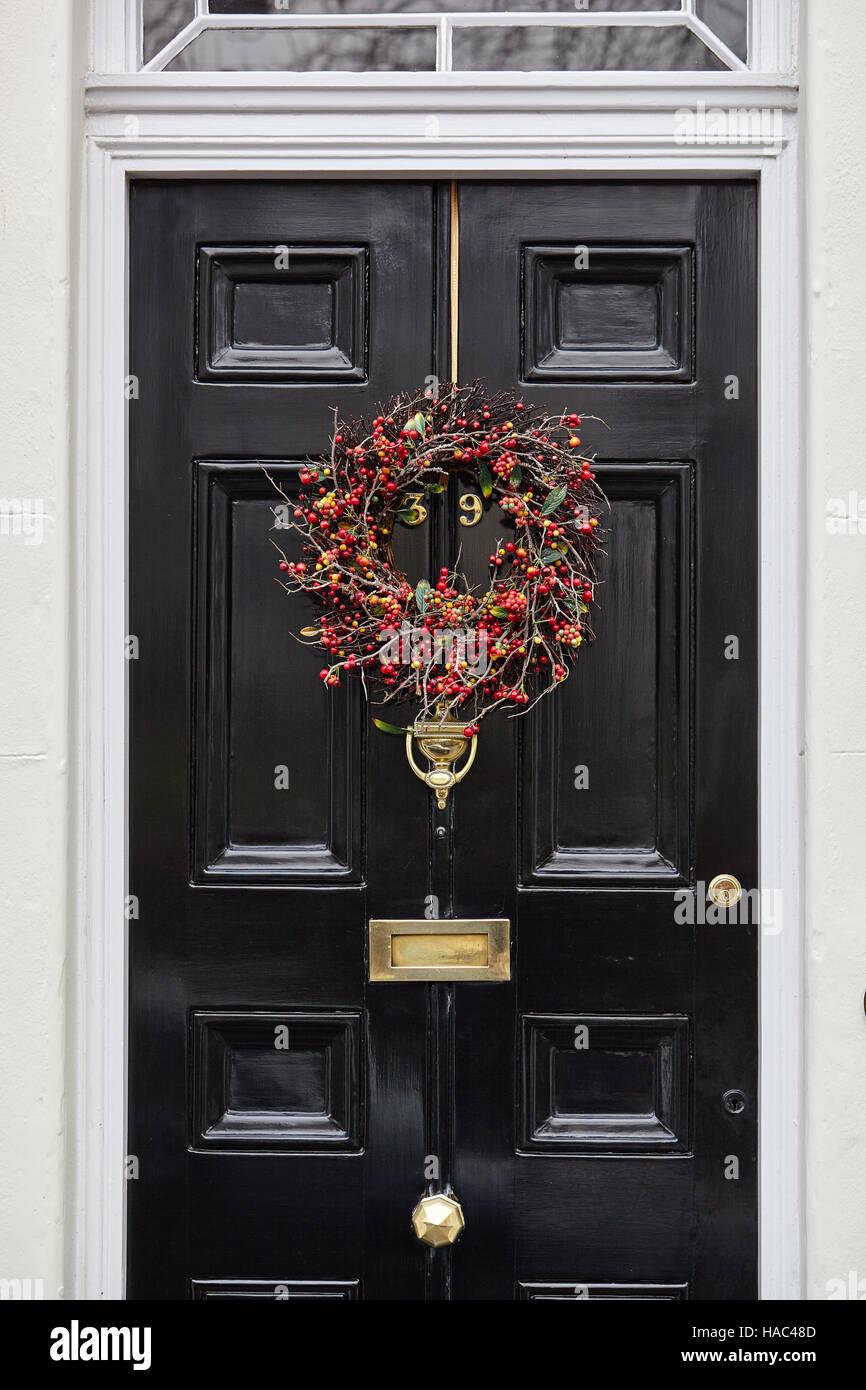 Red Berries Christmas Wreath On Black Front Door Stock Photo