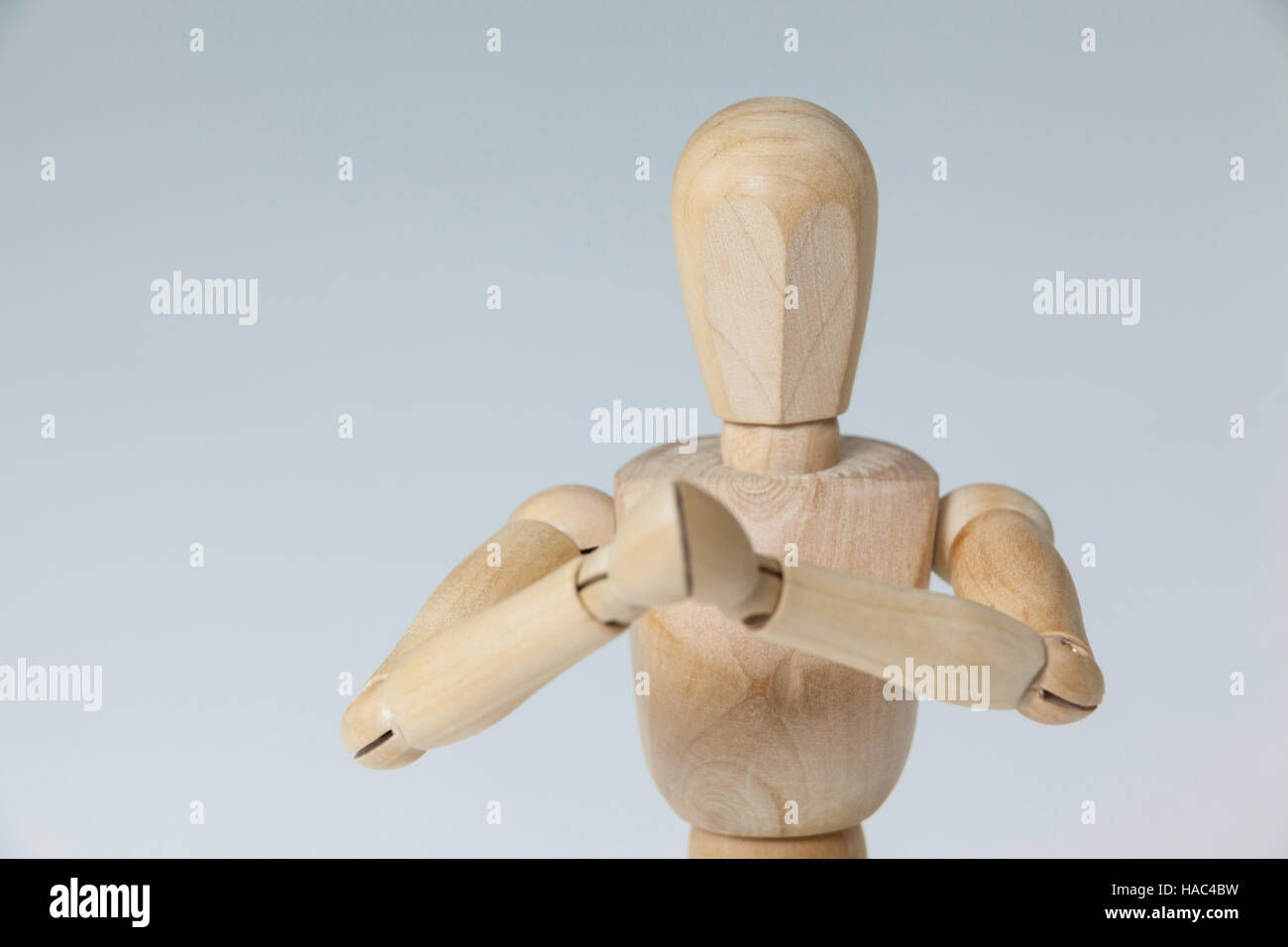 Wooden figurine with both hands joined - Stock Image