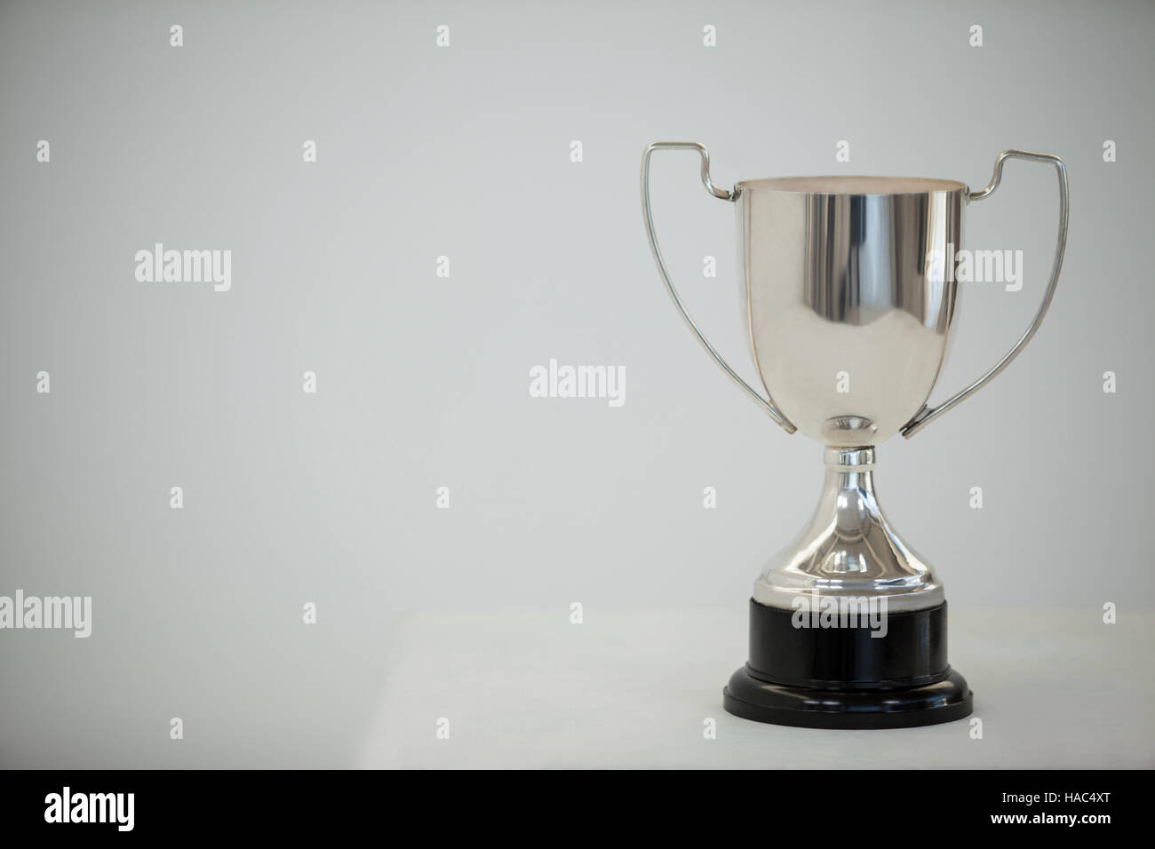 Silver trophy on grey background - Stock Image