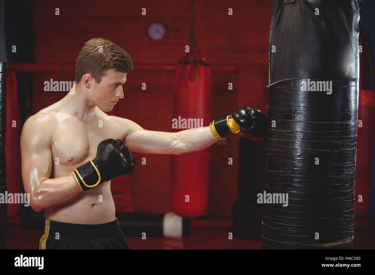 Boxer punching a boxing bag - Stock Image
