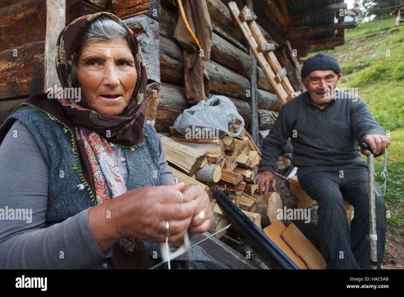 ld couple in Savsat province in Artvin,Turkey. Old woman knit the traditional wool sock for winter in front of her - Stock Image