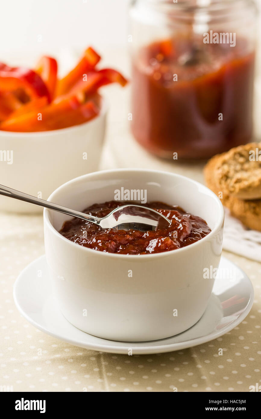 Homemade red bell pepper relish in a bowl - Stock Image