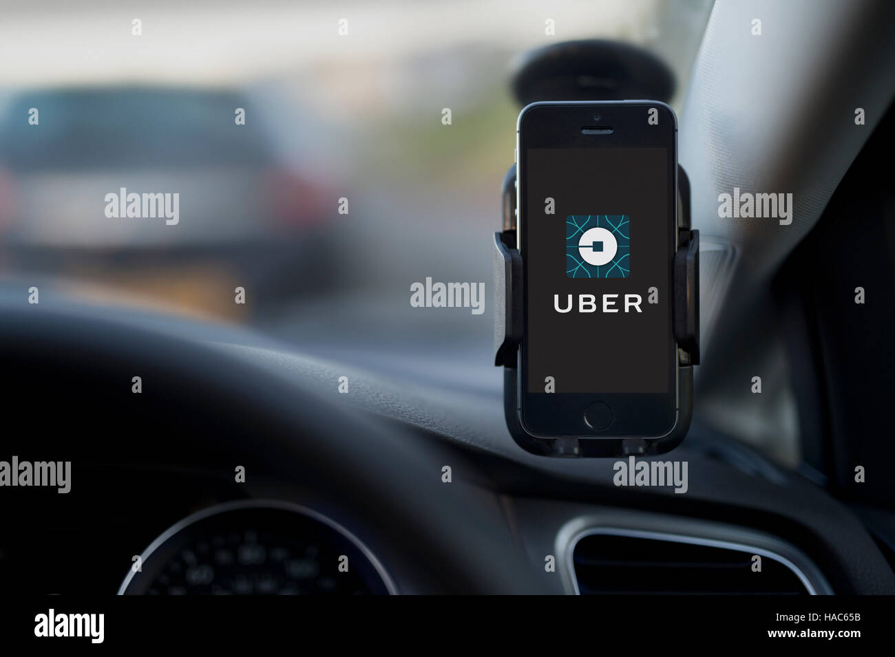 The interior of an Uber taxi with an iPhone fixed to the car's windscreen featuring the company logo. - Stock Image