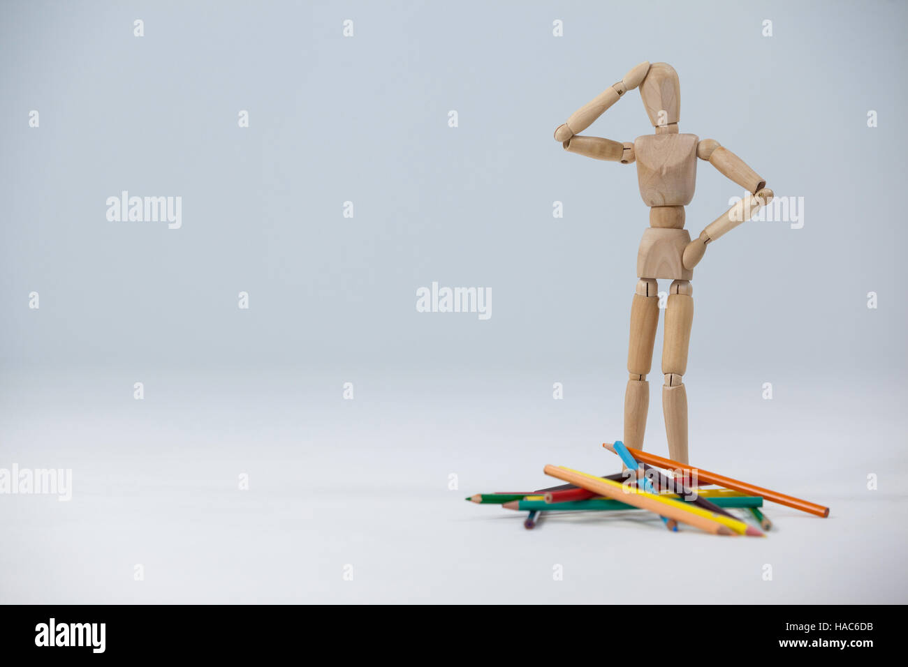 Confused wooden figurine standing near a heap of color pencils - Stock Image