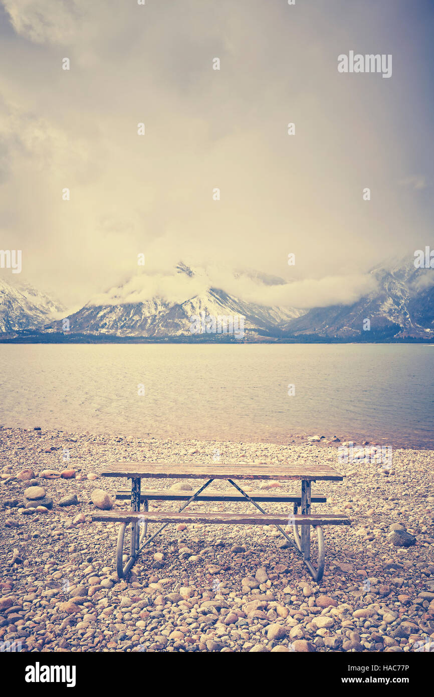 Retro stylized an empty bench with beautiful view over lake, Grand Teton National Park, Wyoming, USA. - Stock Image