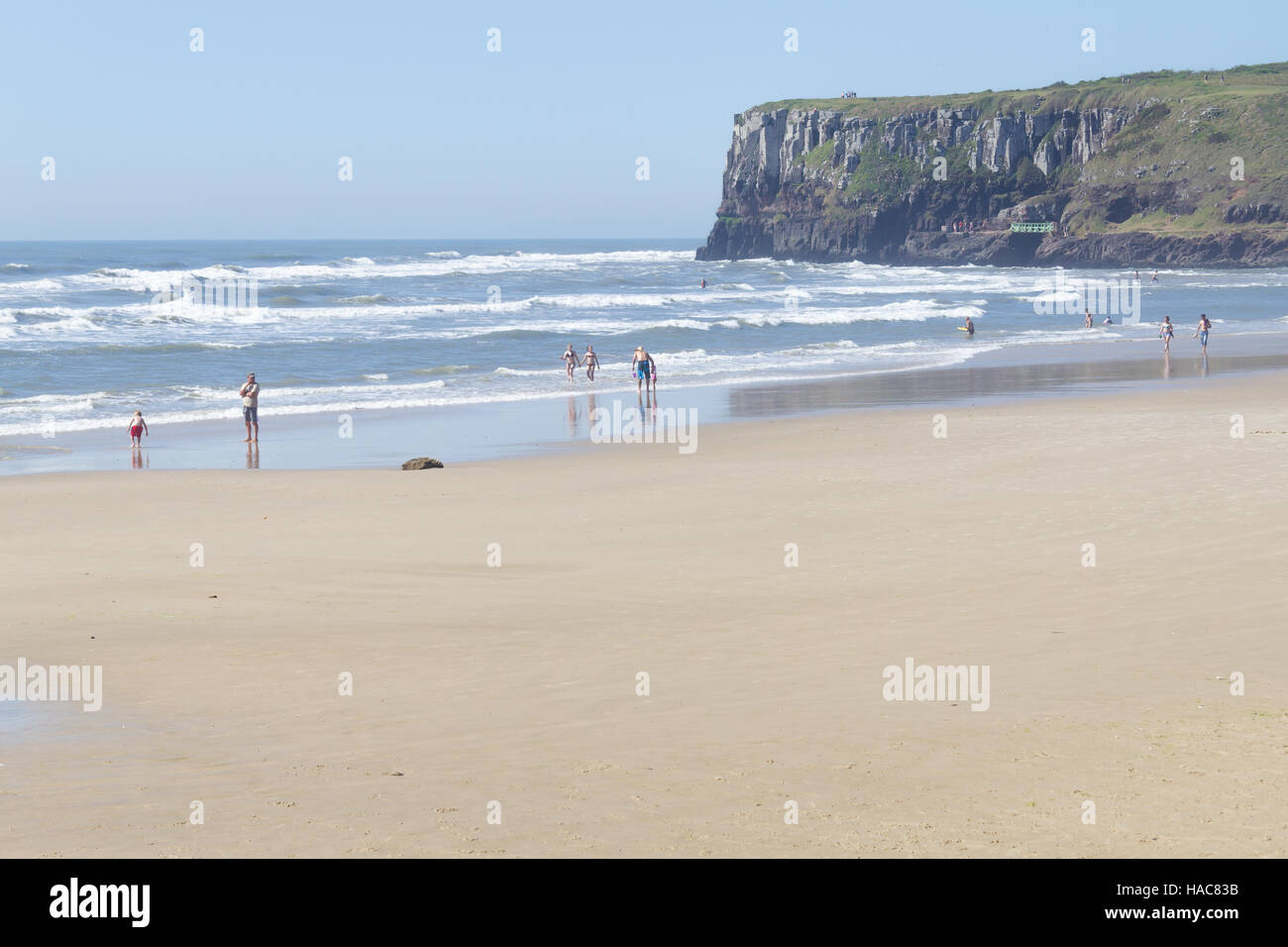 Sunny day with waves and blue sky at Torres, Rio Grande do Sul. Cliffs in background. - Stock Image