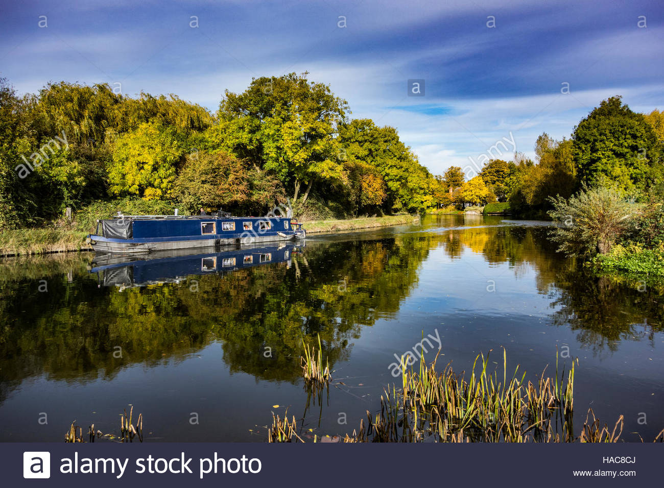 Narrowboat on the River Cam near to Fen Ditton with the reflection of the autumn colours in the water. - Stock Image